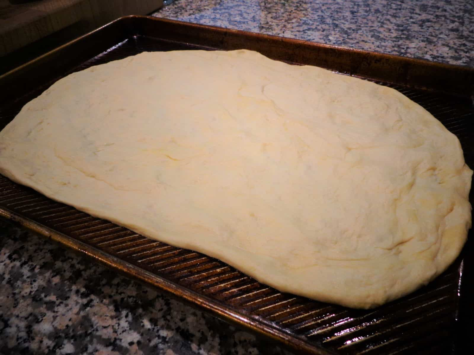 pizza dough spread on a sheet pan