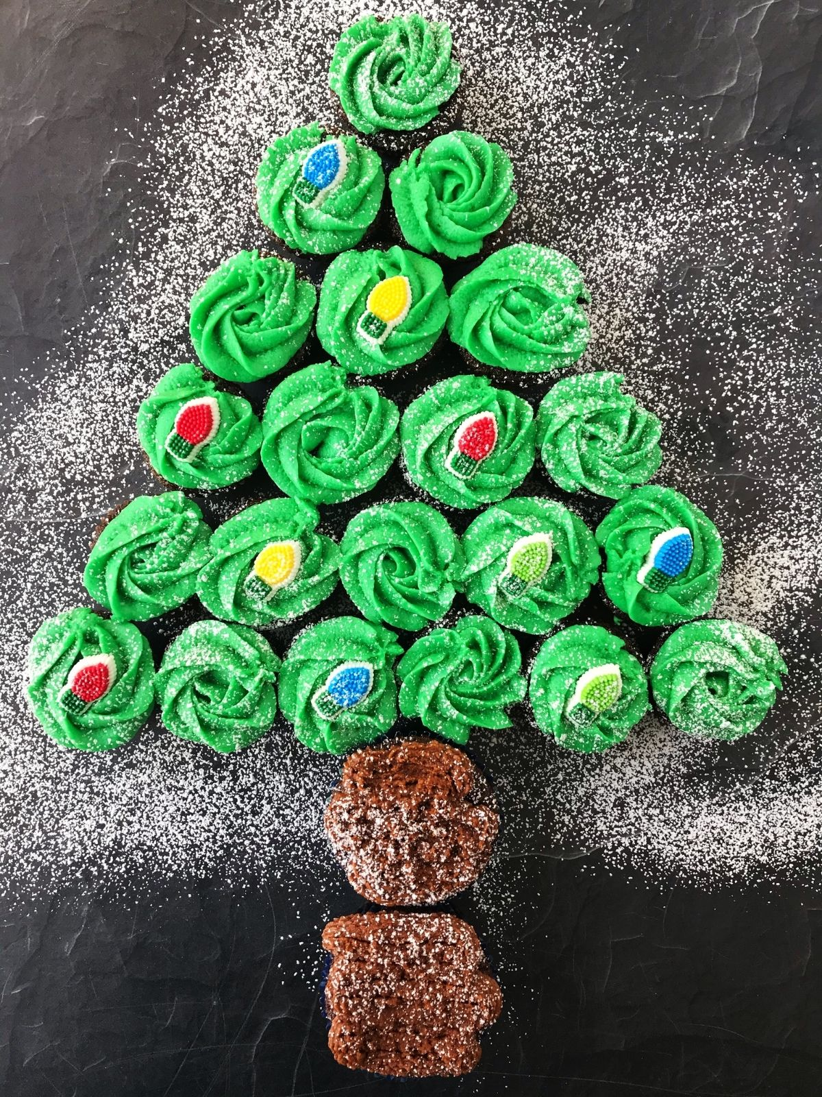 cupcakes arranged in Christmas tree from with a dusting of powdered sugar