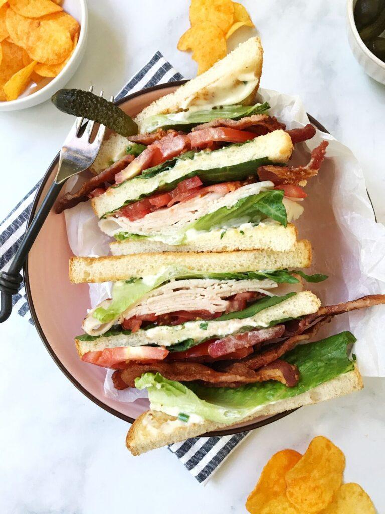 turkey club sandwich plated with a pickle