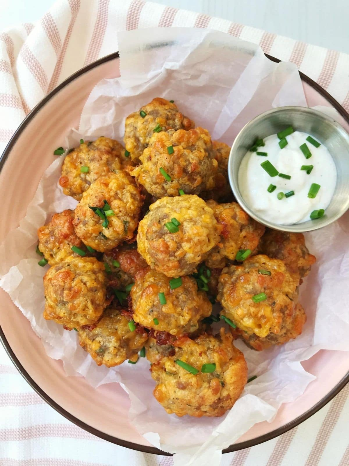 serving bowl of sausage cheese balls with sauce
