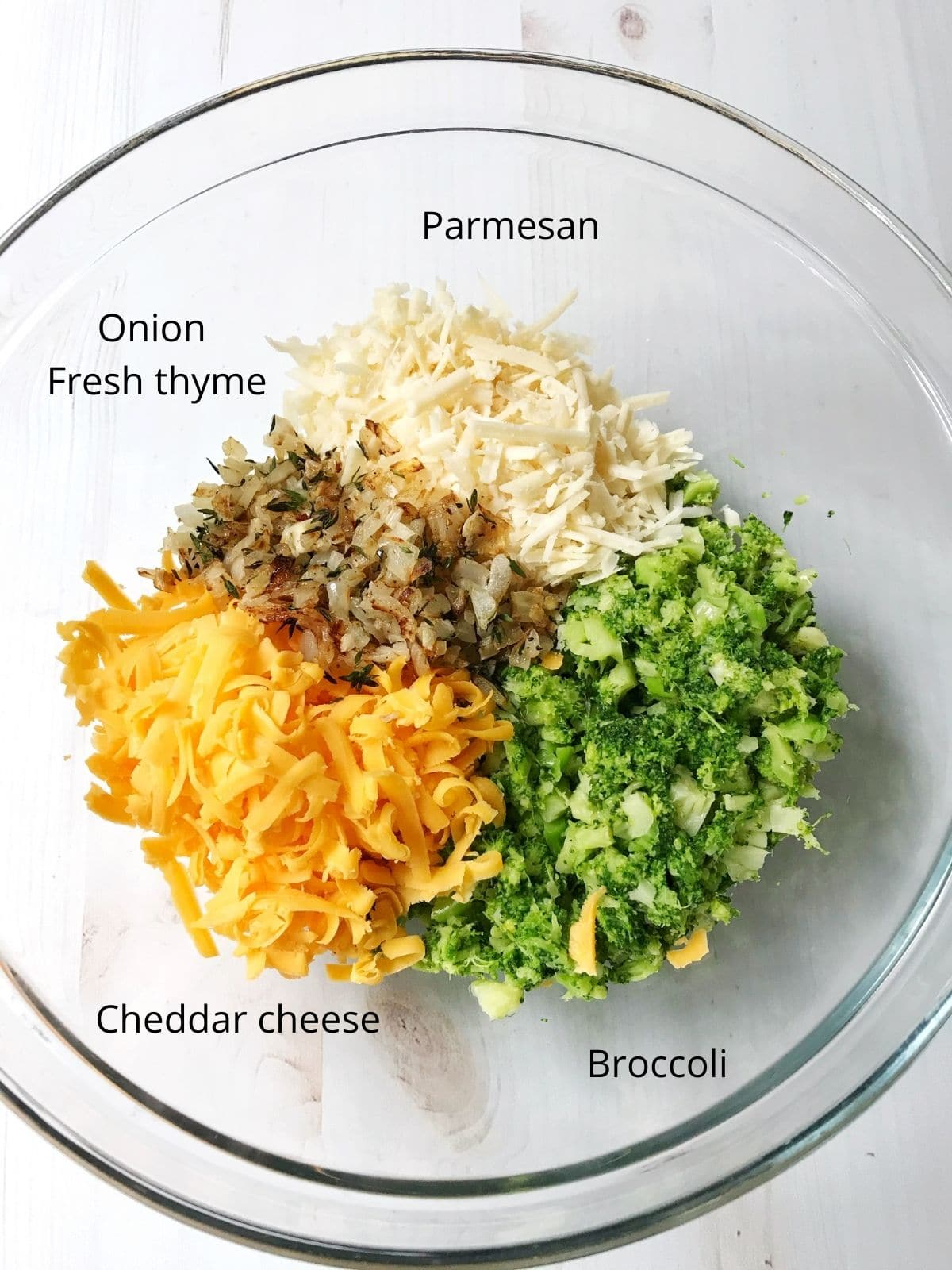bowl of broccoli tart ingredients - broccoli, cheddar, onions, thyme, parmesan