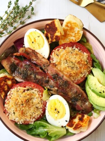 bowl filled with greens, eggs, bacon, roasted tomatoes