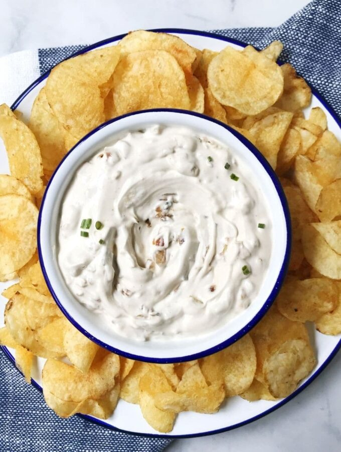 bowl of onion dip on a plate with chips