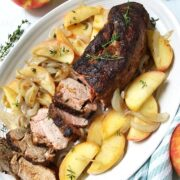 platter of pork surrounded by apples and onions