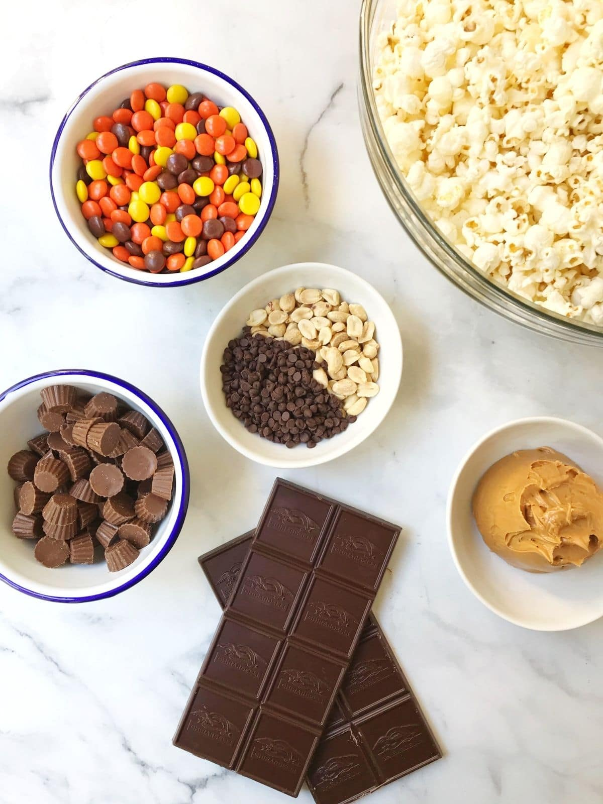 bowls of ingredients - popcorn, chocolate, peanut butter, candy and nuts