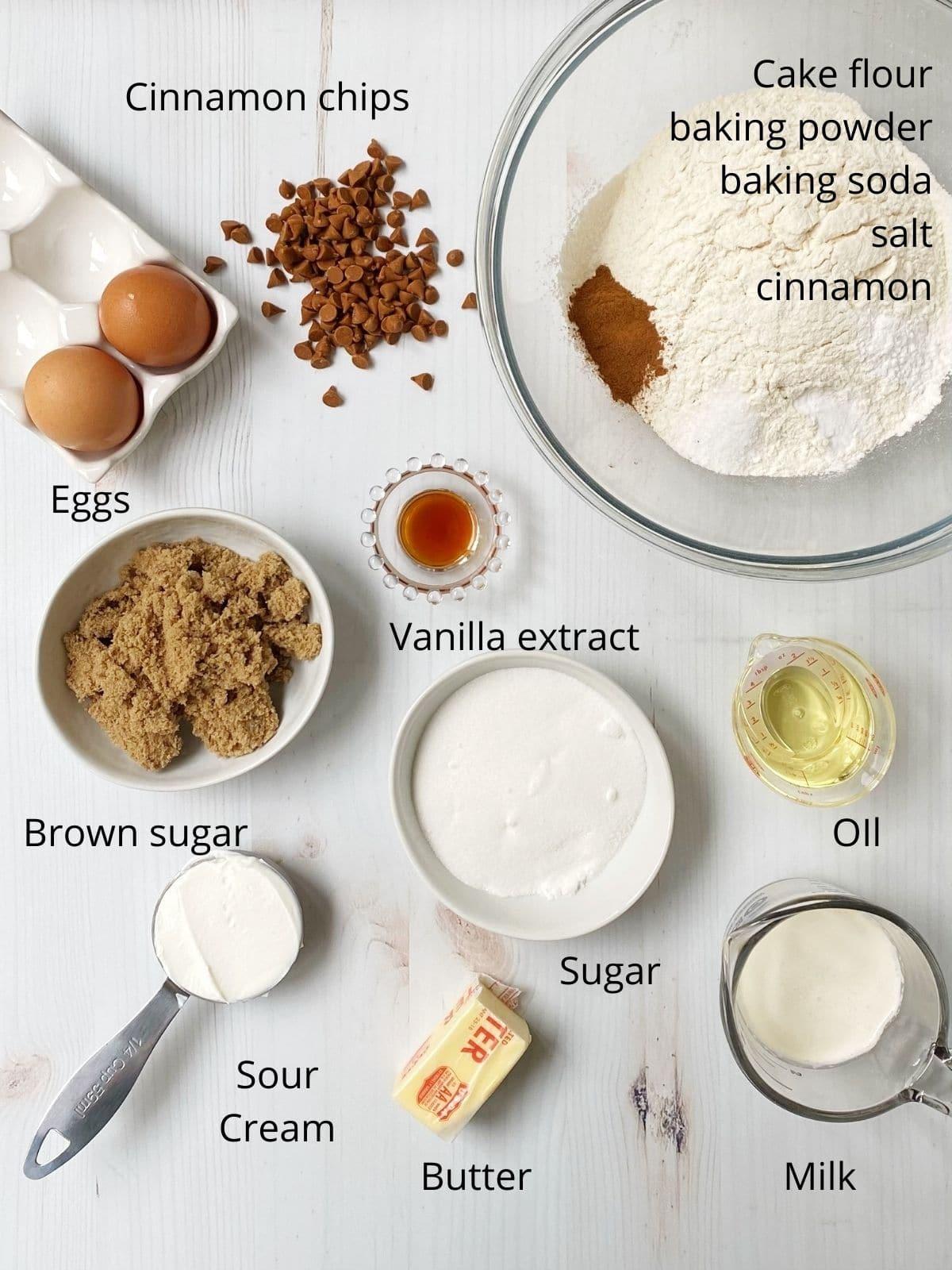 array of eggs, flour, sugars, milk, oil, sour cream, cinnamon chips, baking powder, baking soda, salt, ground cinnamon, butter