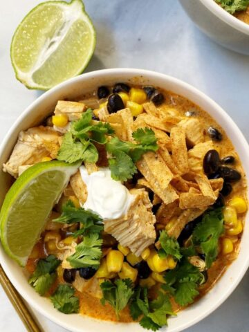 bowl of enchilada soup with lime wedge