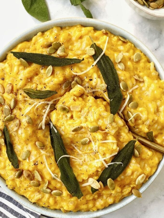 bowl of risotto with sage leaves and serving spoon