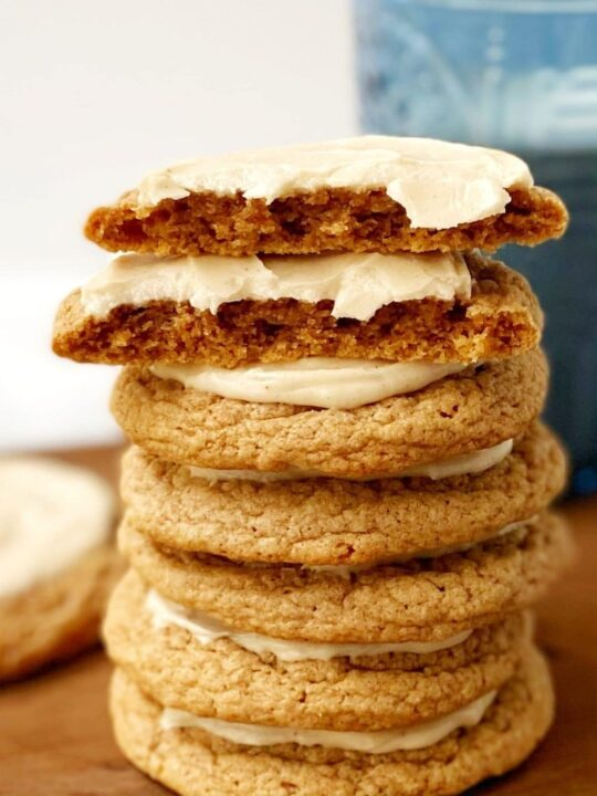 stack of frosted spice cookies with one cookie broken in half