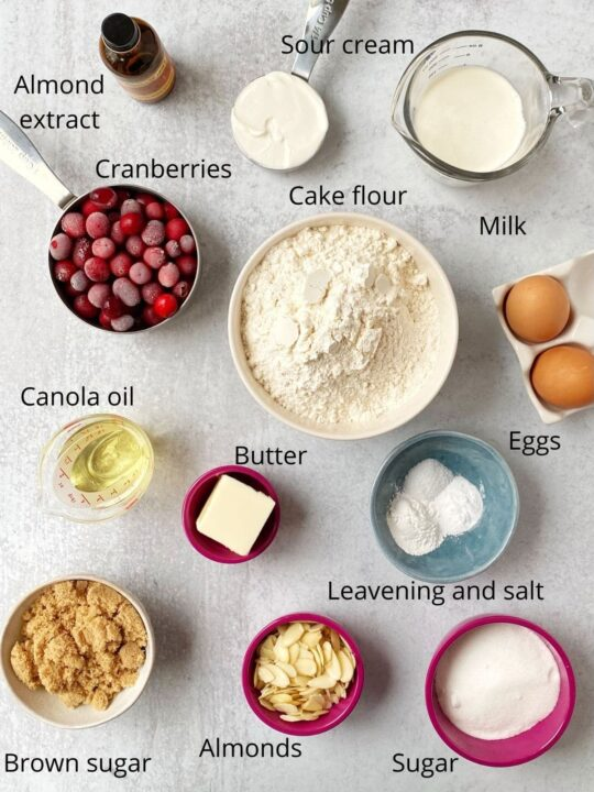 array of ingredients including cake flour, leavening, sugars, butter, oil, eggs, cranberries, almonds, sour cream, and milk