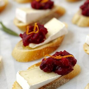 close up of brie and cranberry on a sliced of baguette