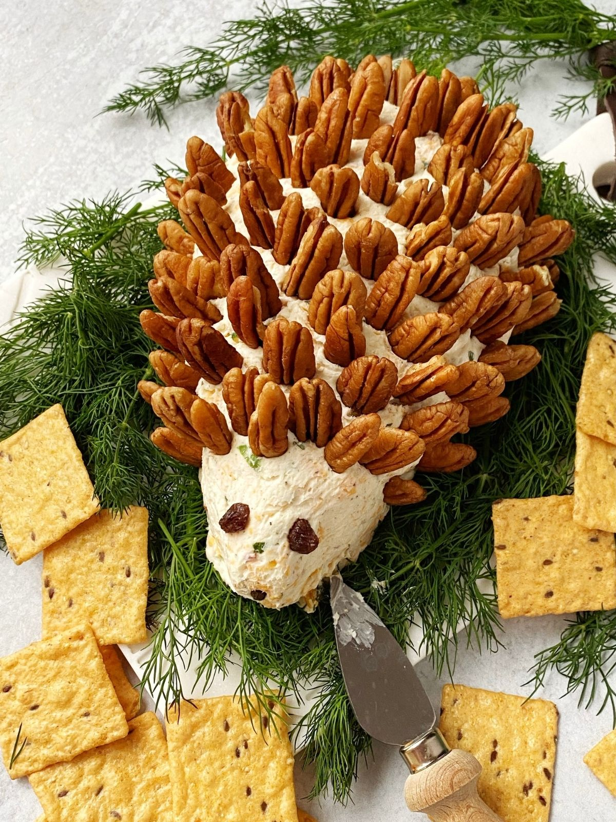 bed of fresh dill topped with cheeseball decorated with pecans