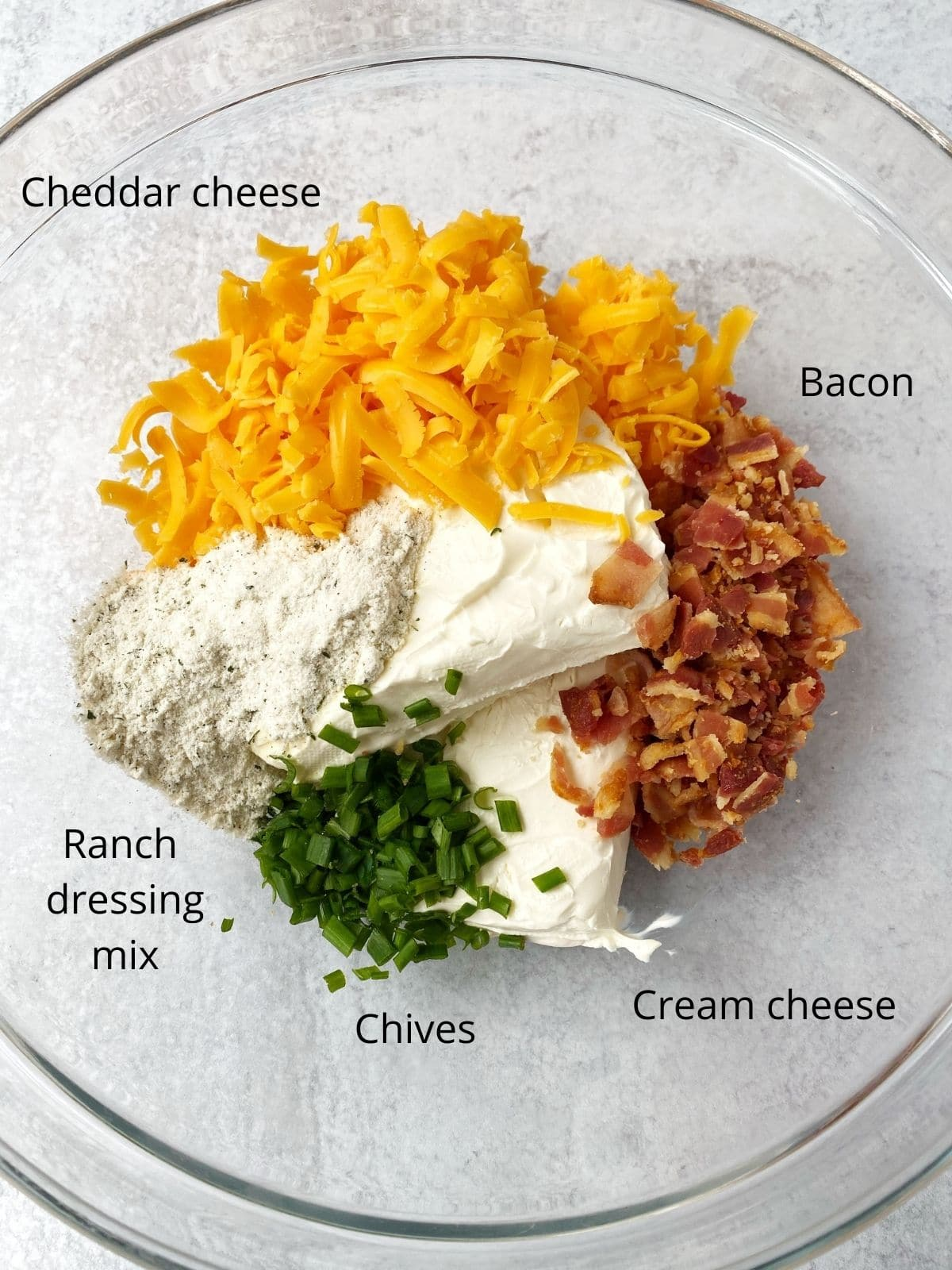 cheeses, bacon, ranch seasoning, and chives in a bowl