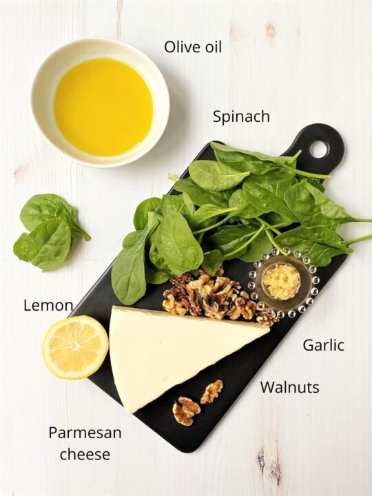 board with spinach, parmesan, garlic, walnuts, lemon, and oil for pesto