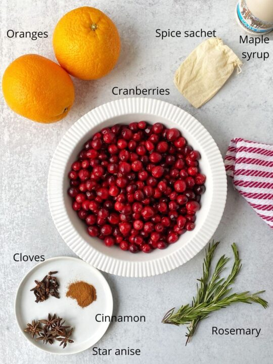 dish of cranberries, oranges, plate of spices, rosemary sprigs, and syrup