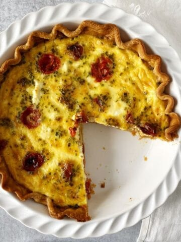 quiche in a pie plate with a slice gone