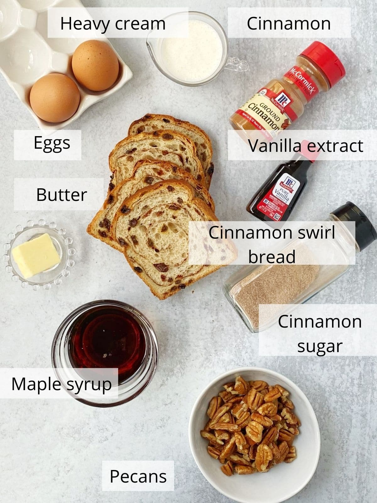 ingredients for french toast including bread, eggs, cream, butter, syrup, pecans, and seasonings