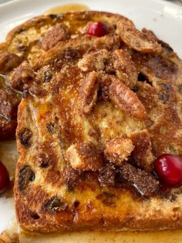 sliced of french toast on plate with pecans and syrup