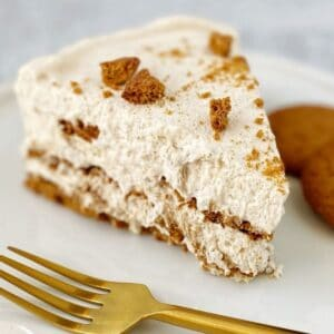 slice of cake on a plate with gingersnap cookies and a fork