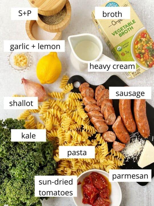 board with kale, sausage, pasta, cheese, shallots, and seasonings