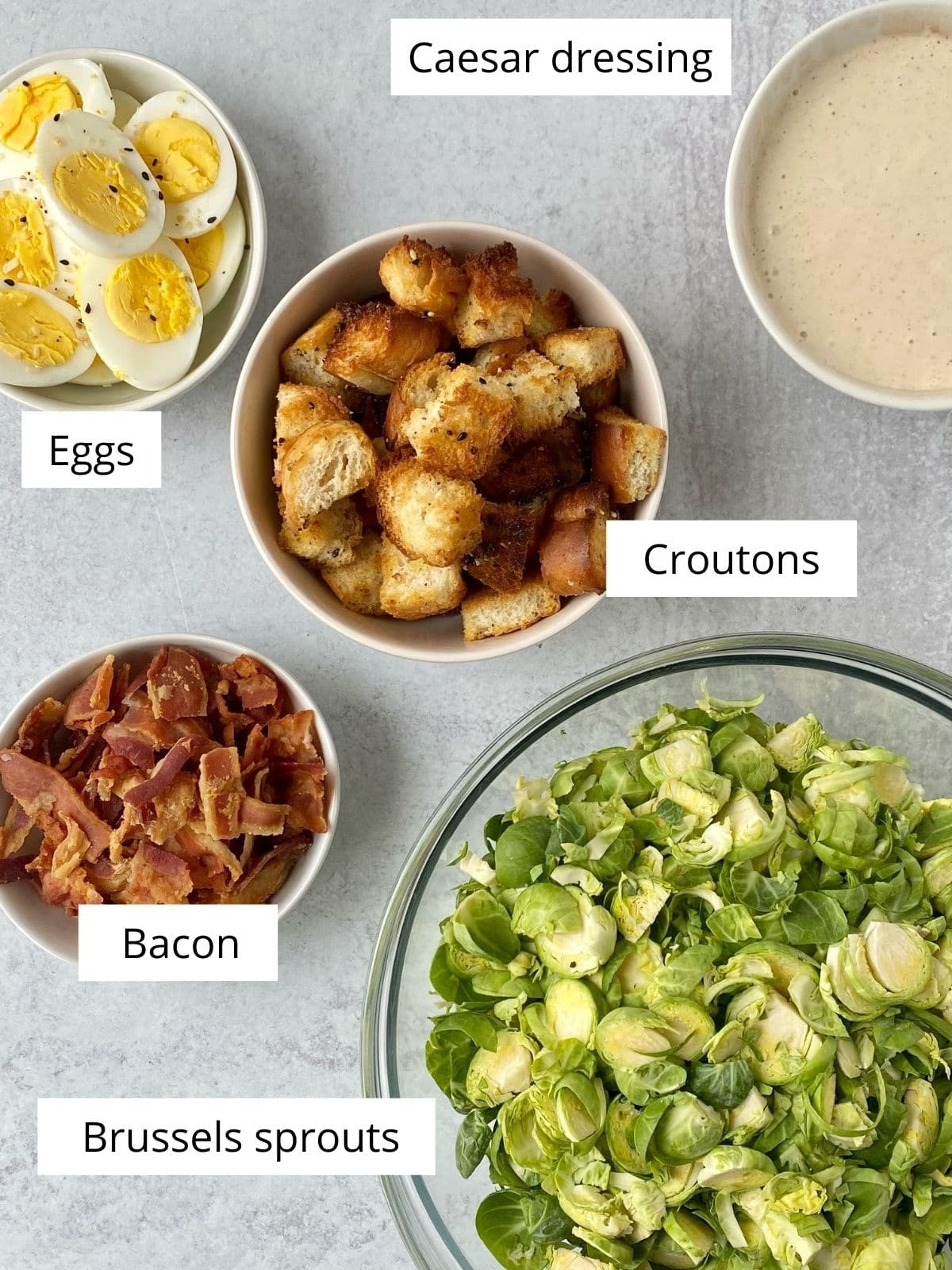 bowls of brussels sprouts, bacon, croutons, eggs, and dressing