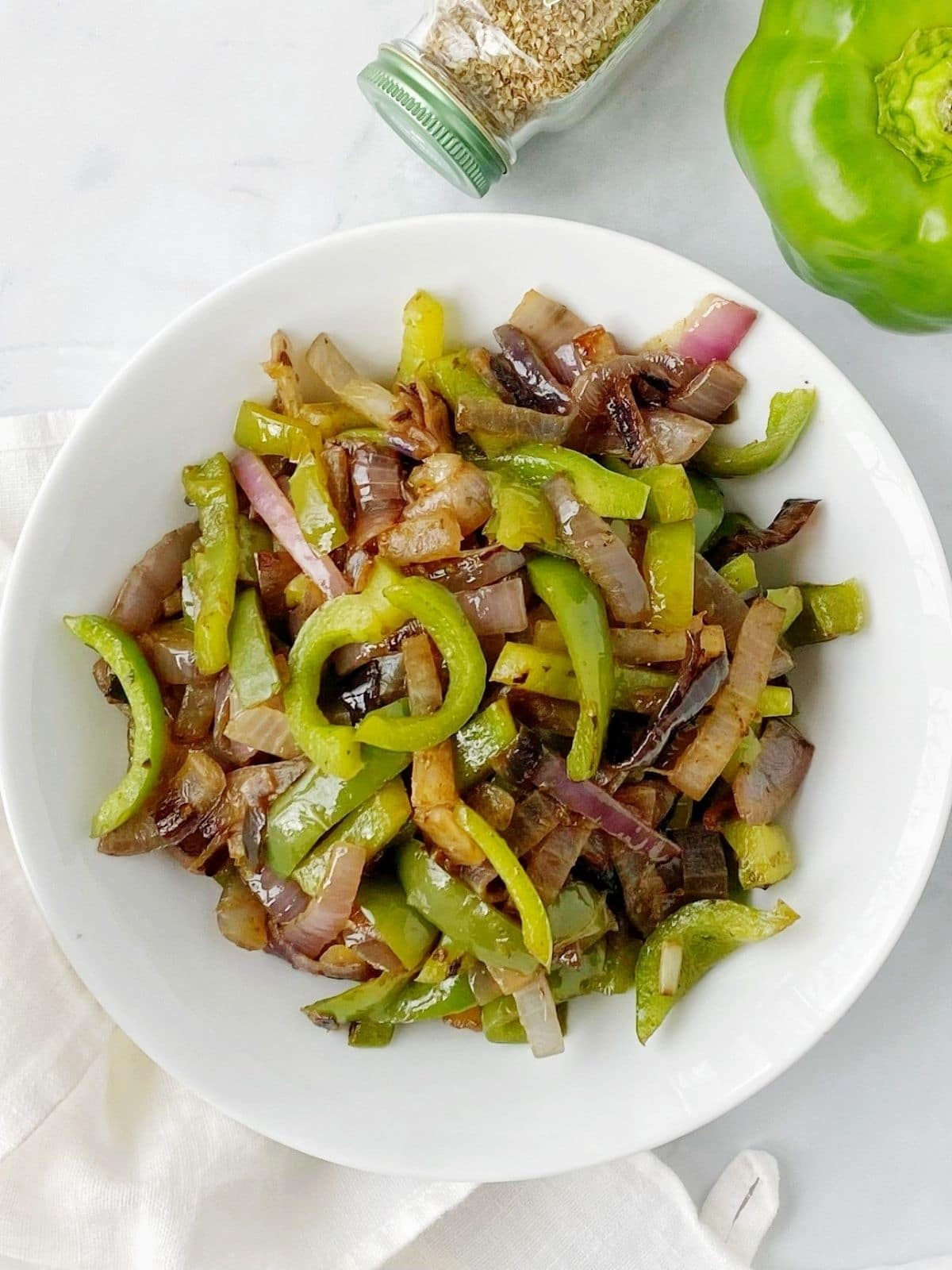 white bowl of sauteed peppers and onions