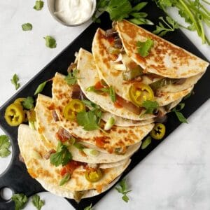 quesadillas arranged on a board with garnishes