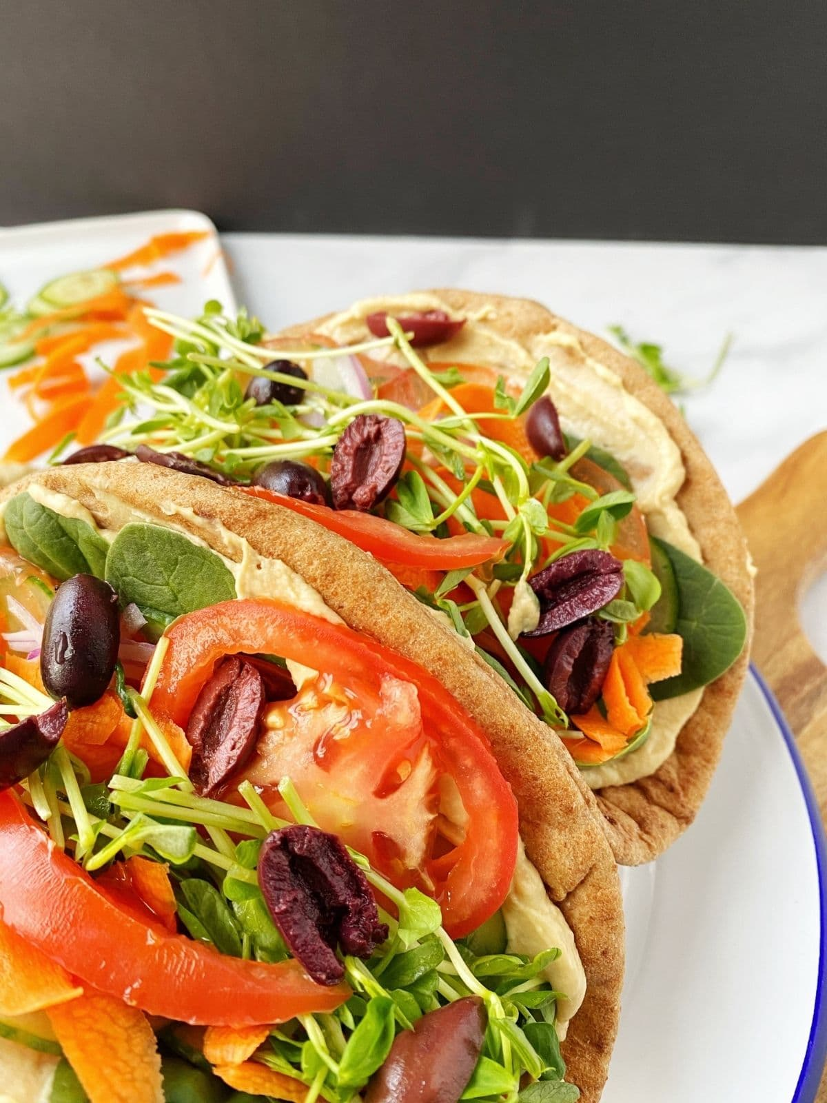 close up of veggies and hummus stuffed pita bread