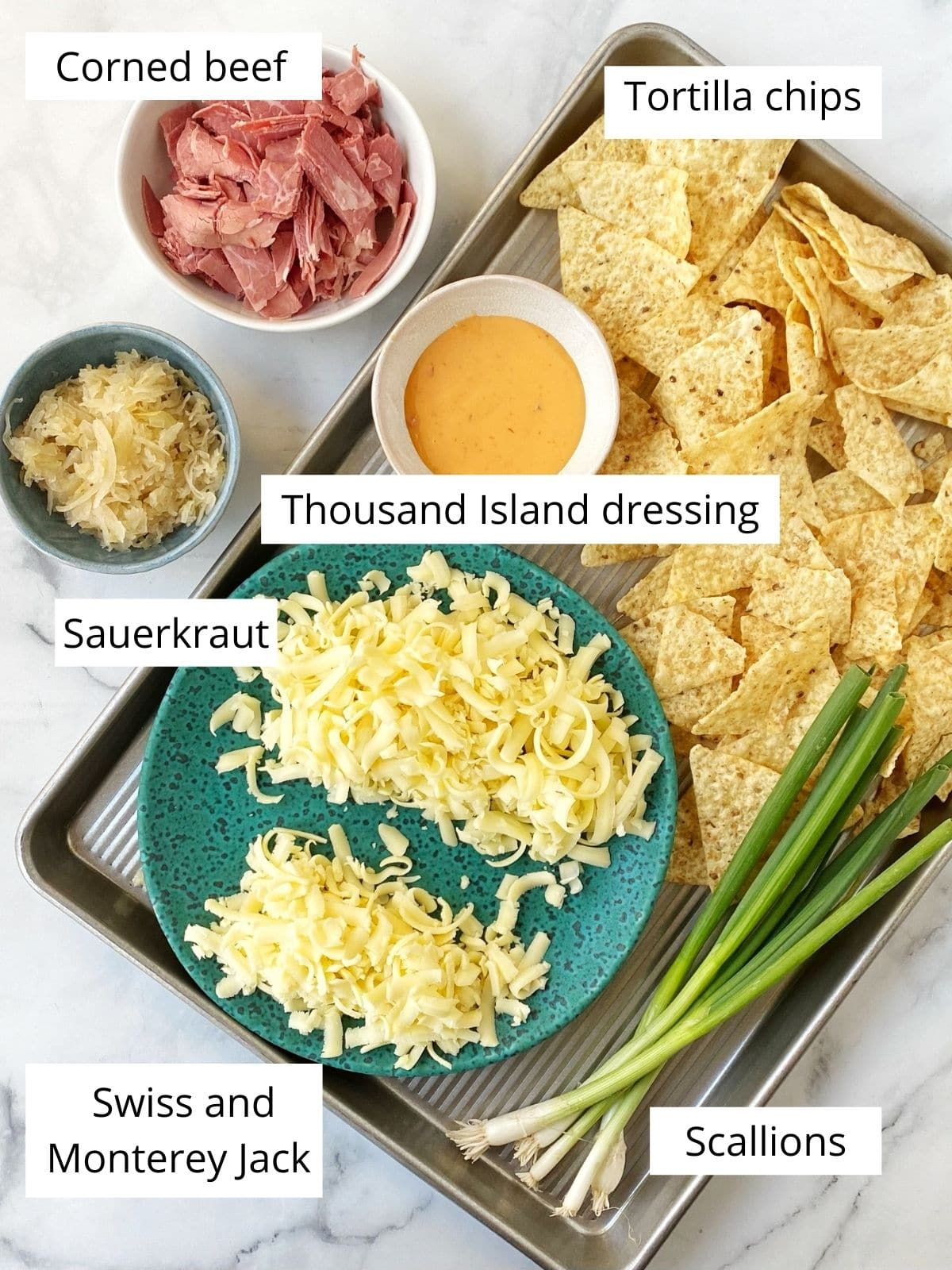 pan of portioned ingredients - chips, cheese, scallions, corned beef, sauerkraut, dressing