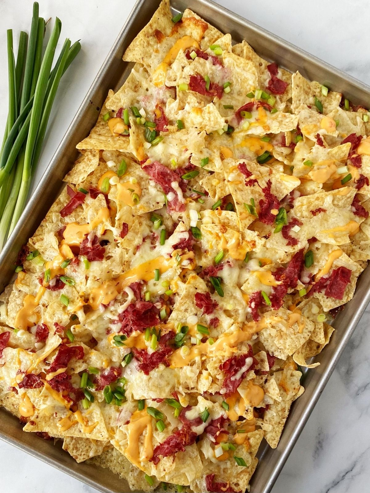 sheet pan of nachos with scallions