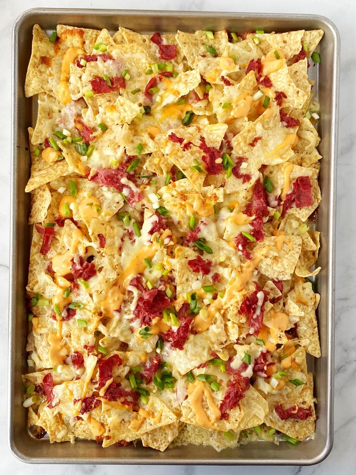 sheet pan of nachos topped with Thousand Island dressing and scallions