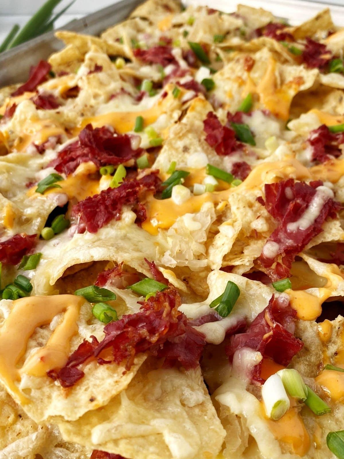 close up of nachos on sheet pan