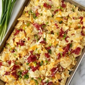 sheet pan of nachos with scallions for garnish