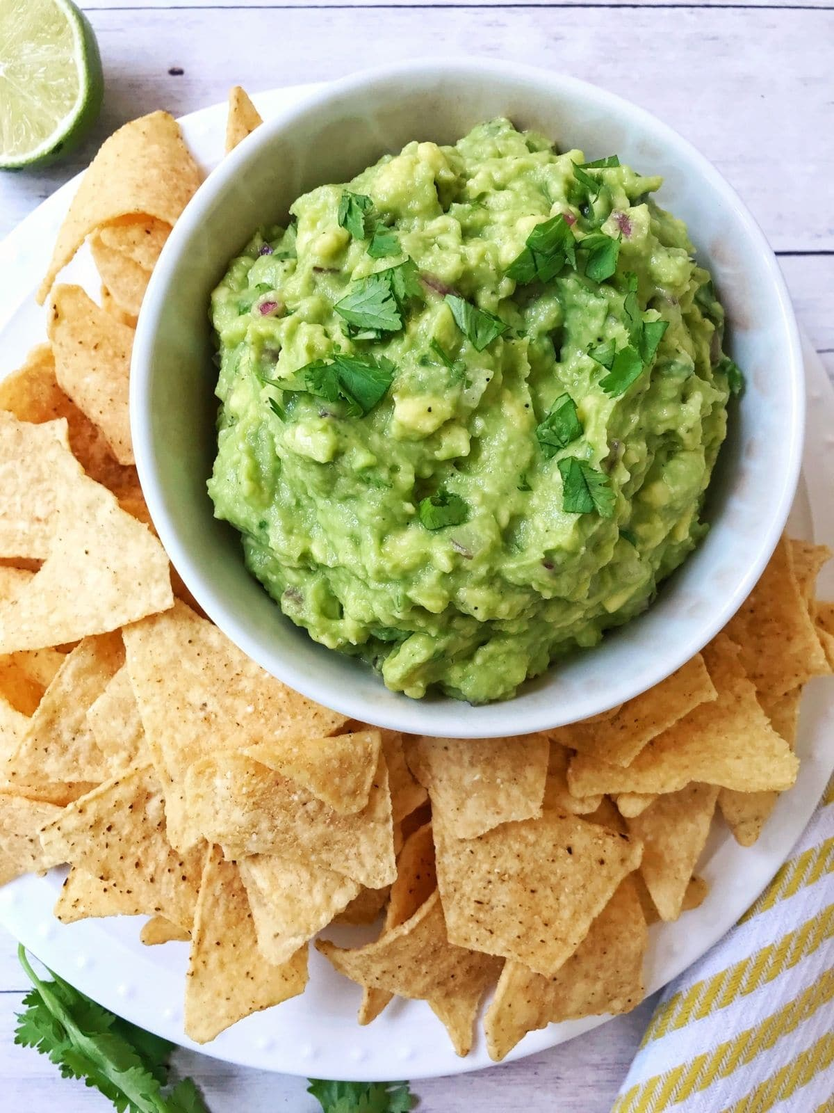 dish of guacamole on a platter with tortilla chips arranged on the side