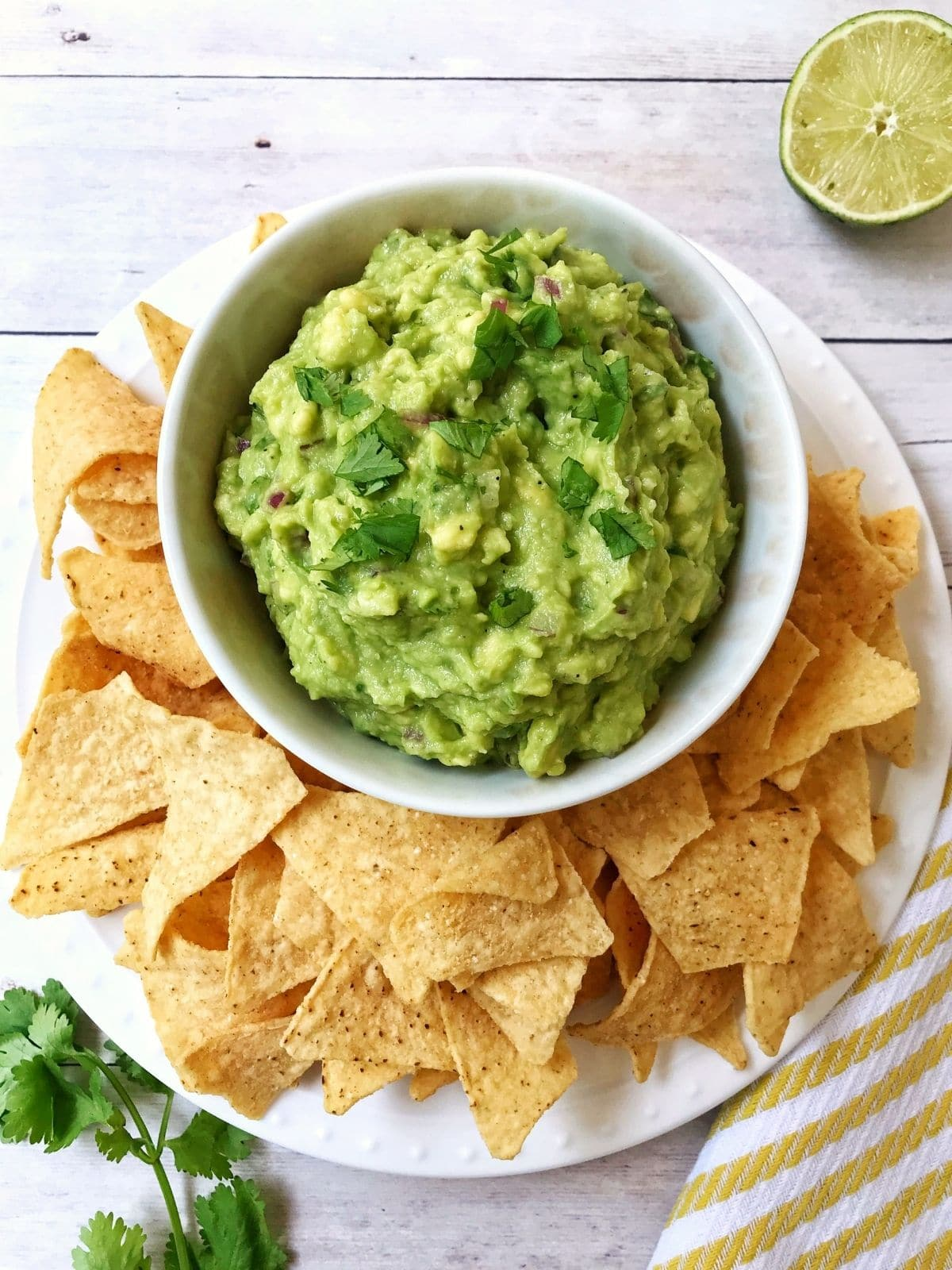 overhead of bowl of guacamole surrounded by chips, lime and cilantro