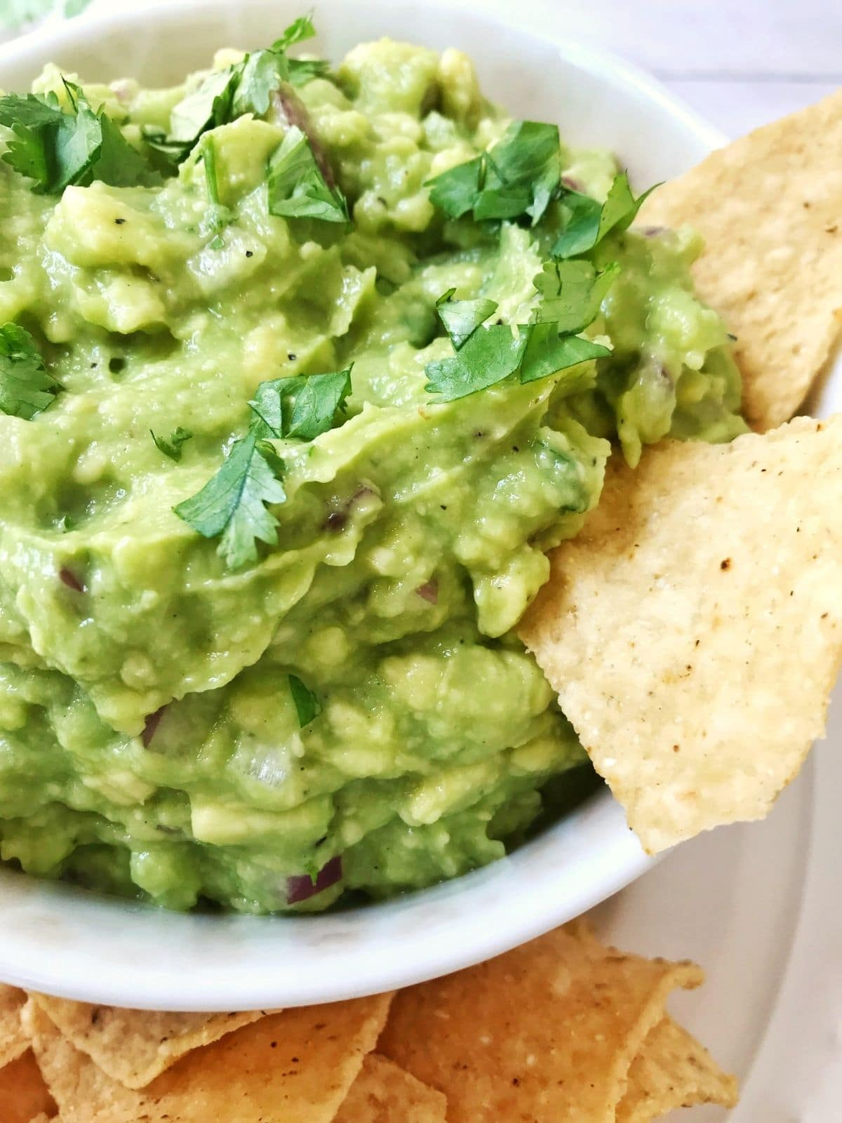 close up of avocado spread with chips digging in