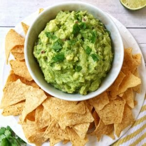 bowl of guacamole on serving platter with chips