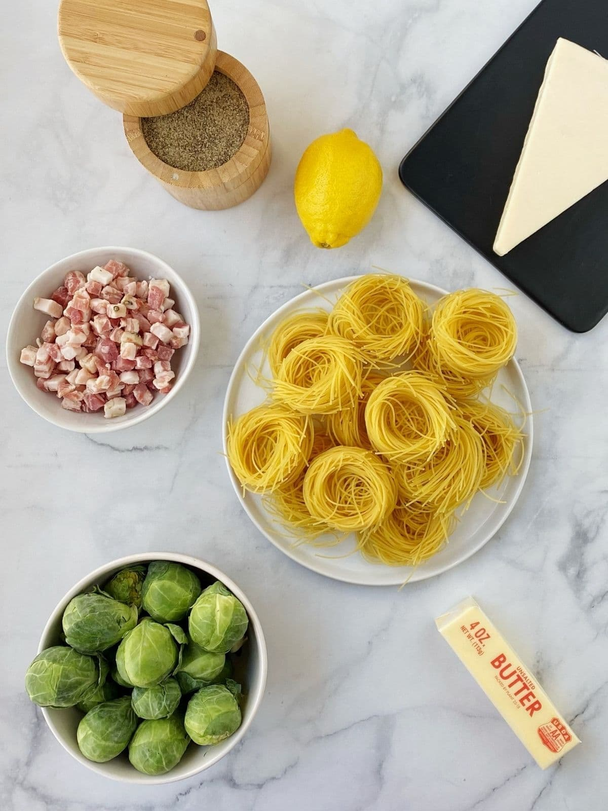 overhead shot of ingredients - sprouts, cheese, pasta, pancetta, lemon, butter