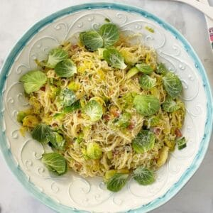 serving bowl of pasta garnished with brussels sprouts leaves