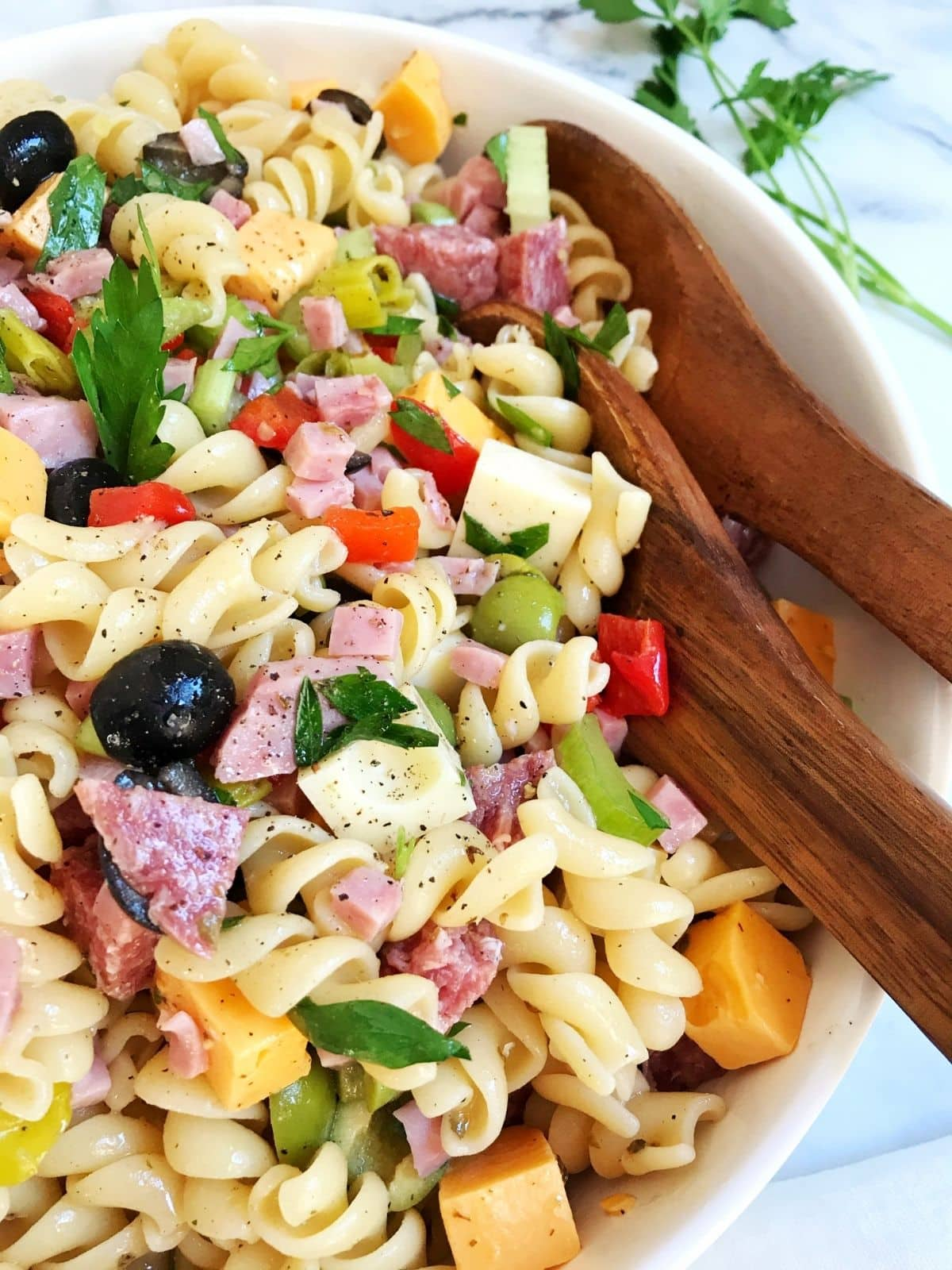 serving spoons in bowl of pasta salad