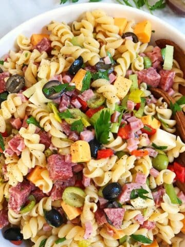 bowl of pasta salad with serving utensils