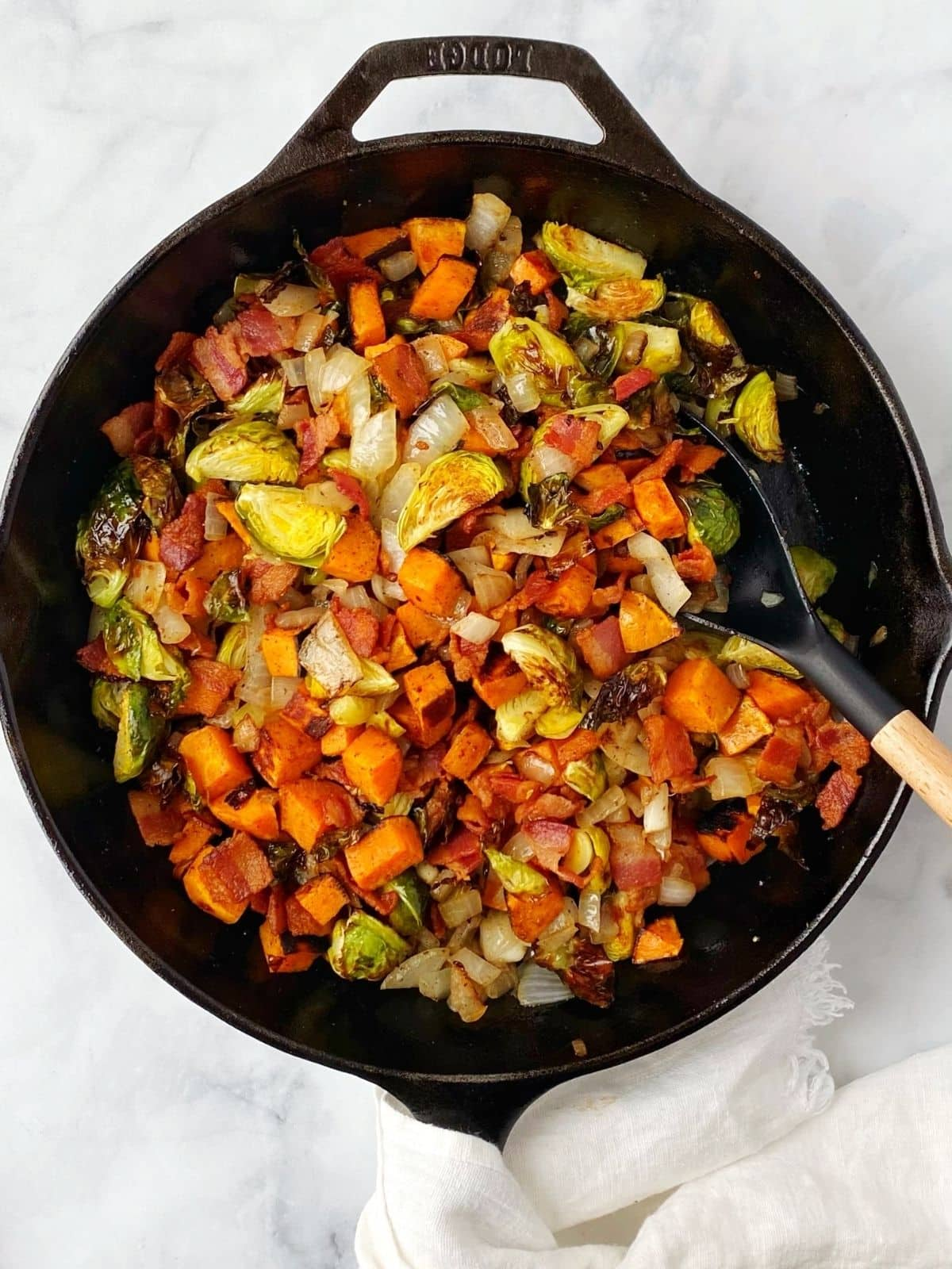 veggies and bacon combined in the skillet