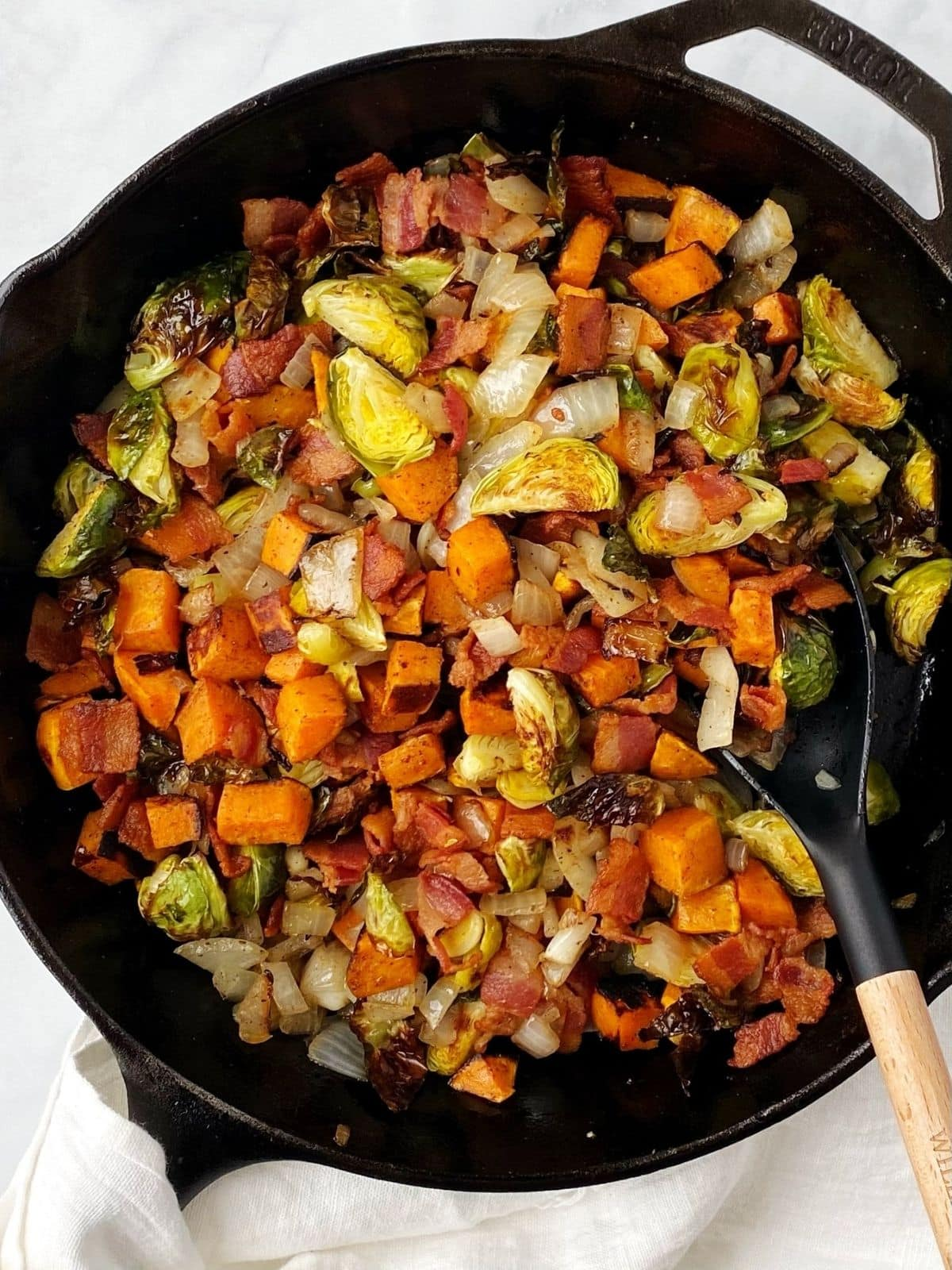 close up of veggies and bacon in the cast-iron skillet
