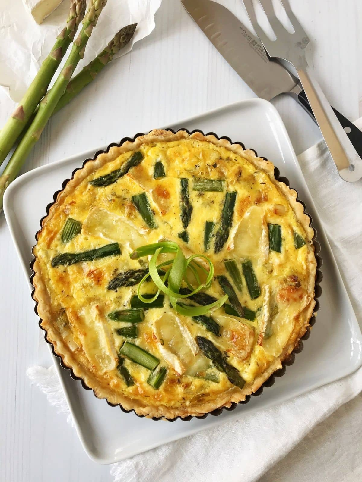 overhead shot of quiche with serving utensils on the side