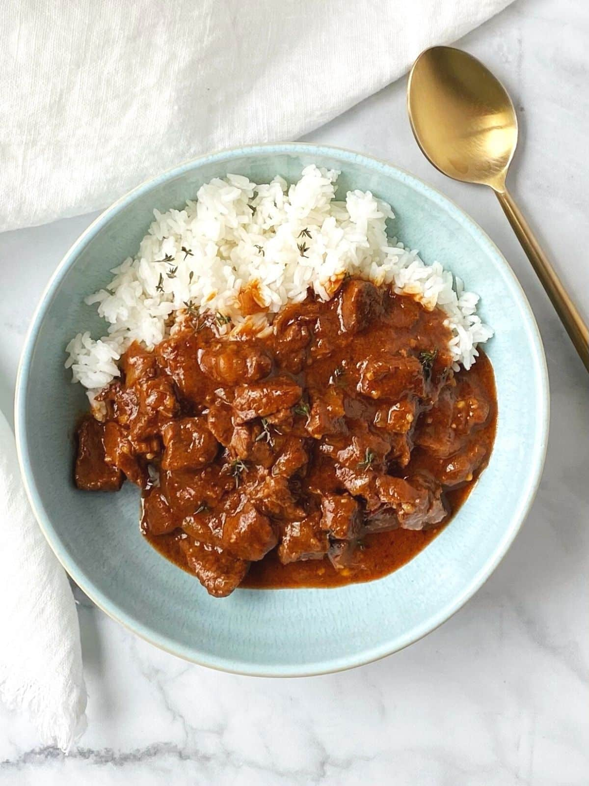 light blue bowl with rice and beef stew
