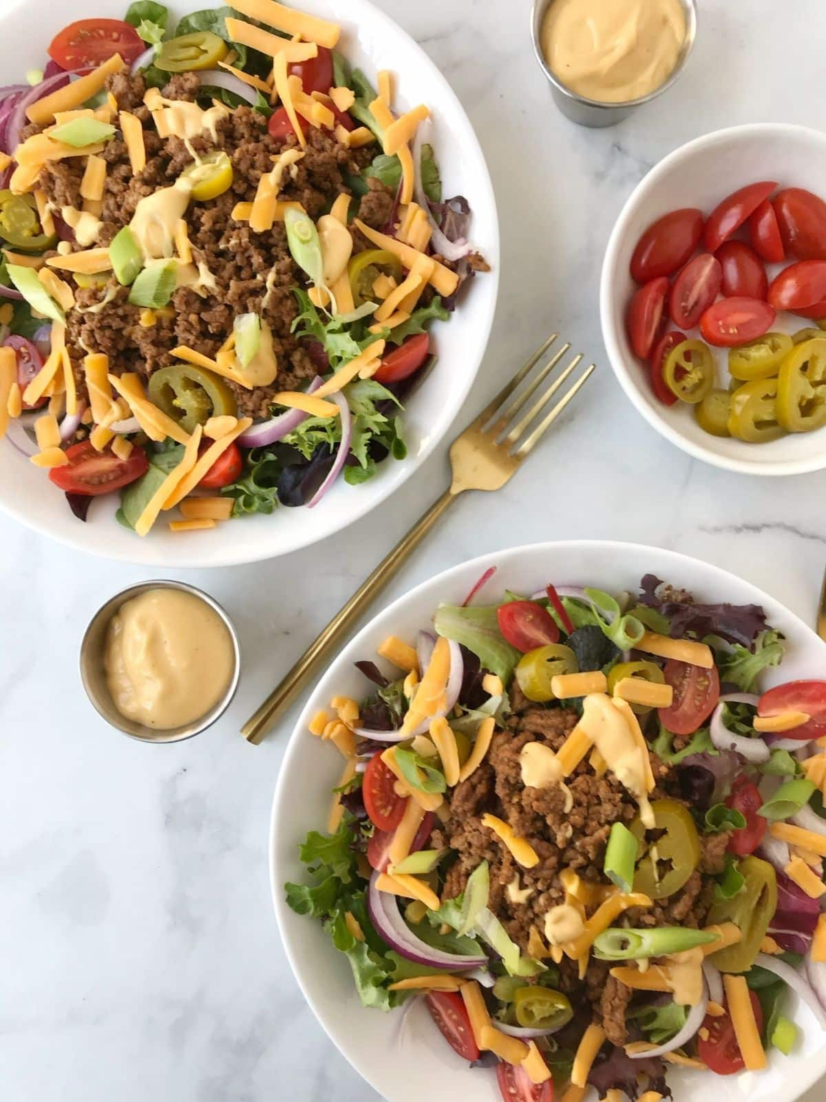 bowls of salad with cheeseburger toppings and dressing on the side