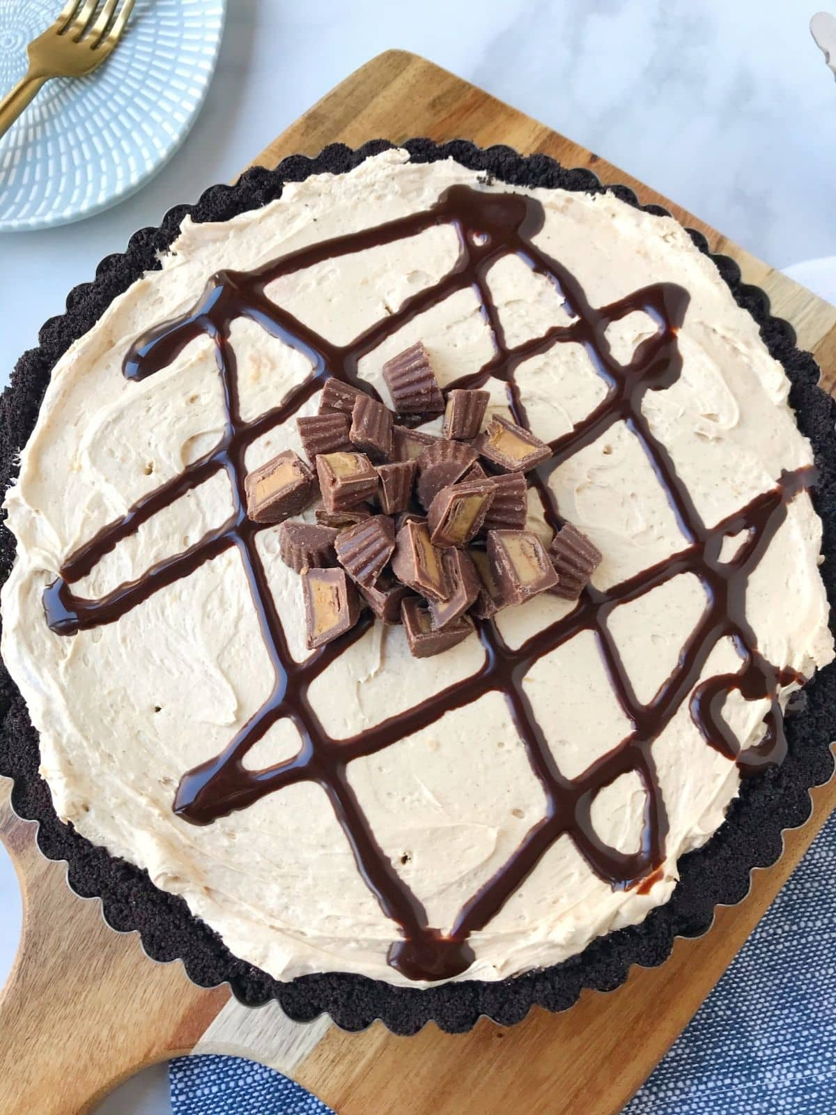 whole peanut butter tart garnished with chocolate sauce and peanut butter cups