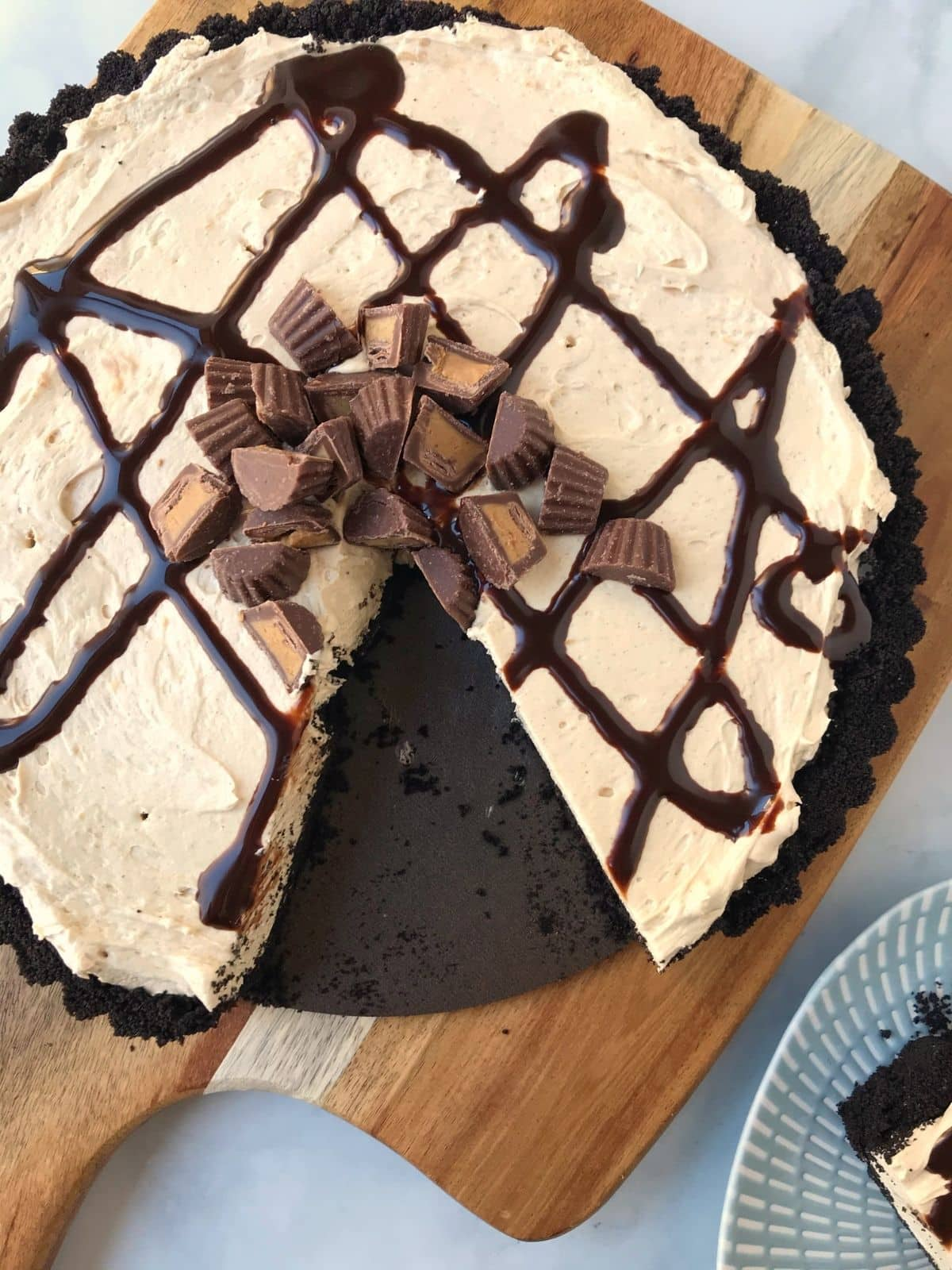 whole tart garnished with peanut butter cups and a slice removed