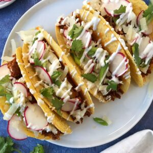 tacos on a plate garnished with crema and cilantro
