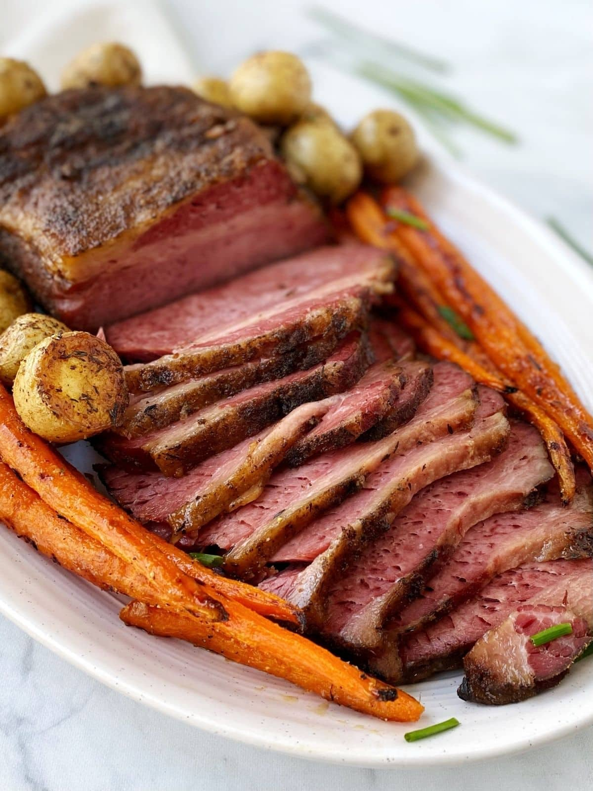 corned beef on a platter with potatoes and carrots